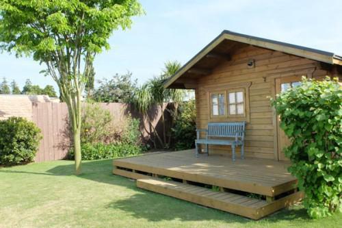 芝、樹、ログハウスのある庭、そして青空